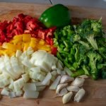 Chopped bell peppers, onions and garlic on board