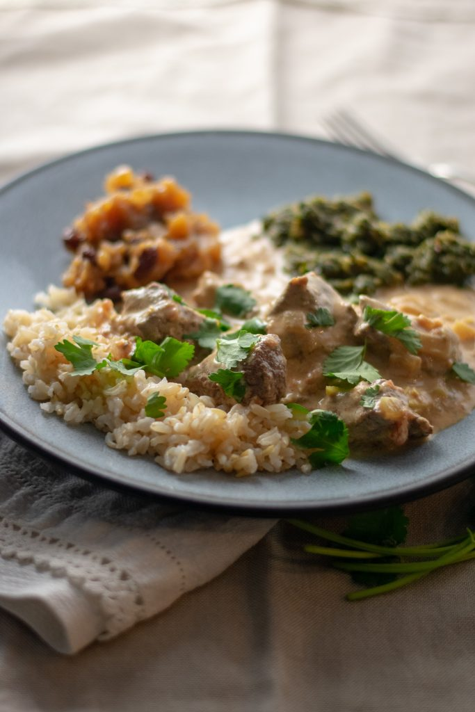 Beef Coconut Milk Curry on plate with chutney and saag