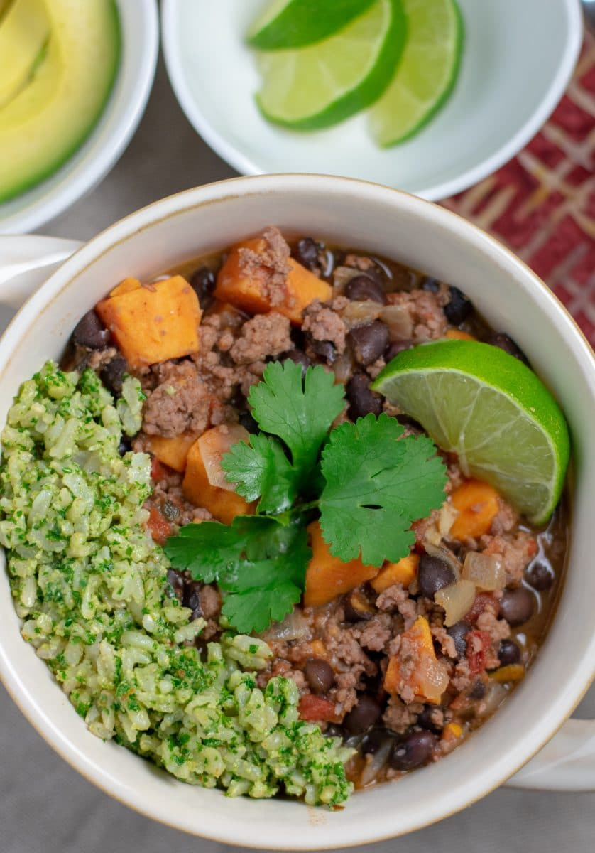 Black Bean Sweet Potato Chili with Nut Pesto Green Rice in white bowl