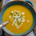 Butternut squash soup in blue bowl with garnishes