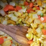 Vegetables in cooking pot with wooden spoon