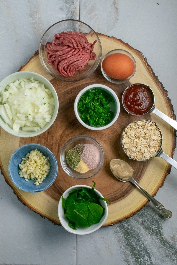 Beef spinach meatballs ingredients on wood board overhead view