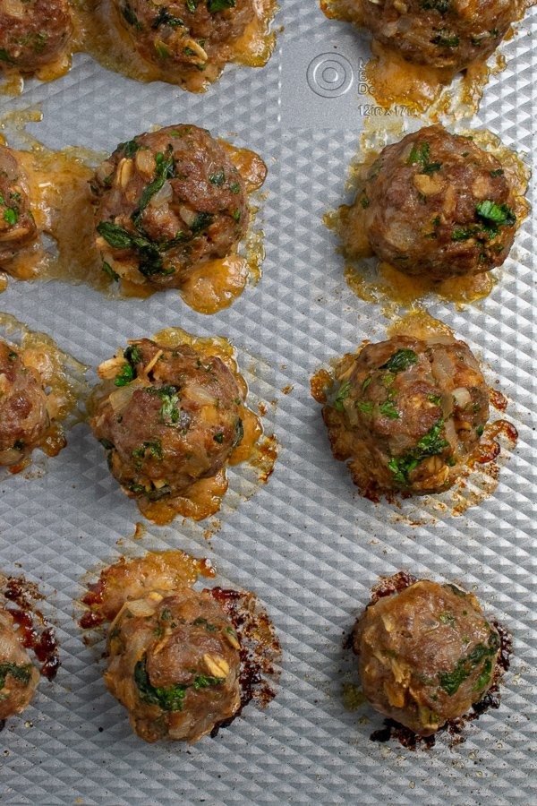 Beef spinach meatballs on silver baking pan closeup