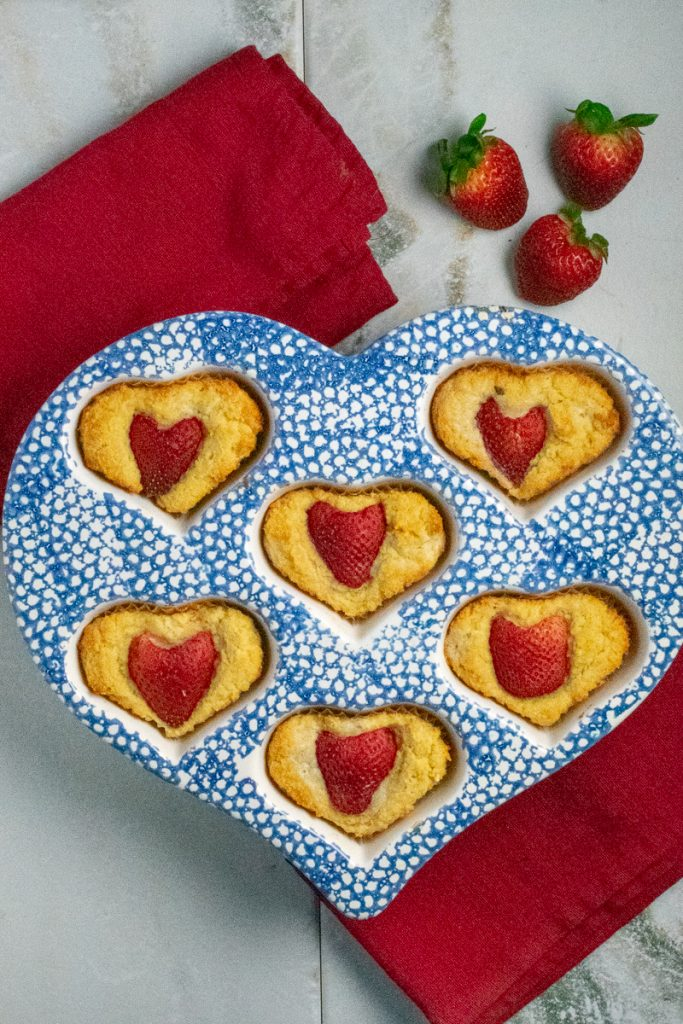 strawberry heart muffins in blue baking pan on red cloth