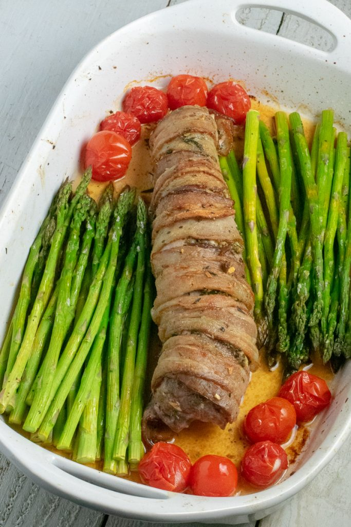 Pork tenderloin with asparagus and tomatoes in white baking dish