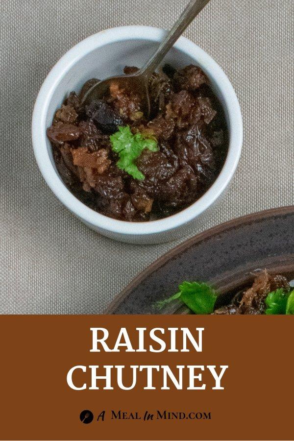 Raisin chutney in white bowl with spoon