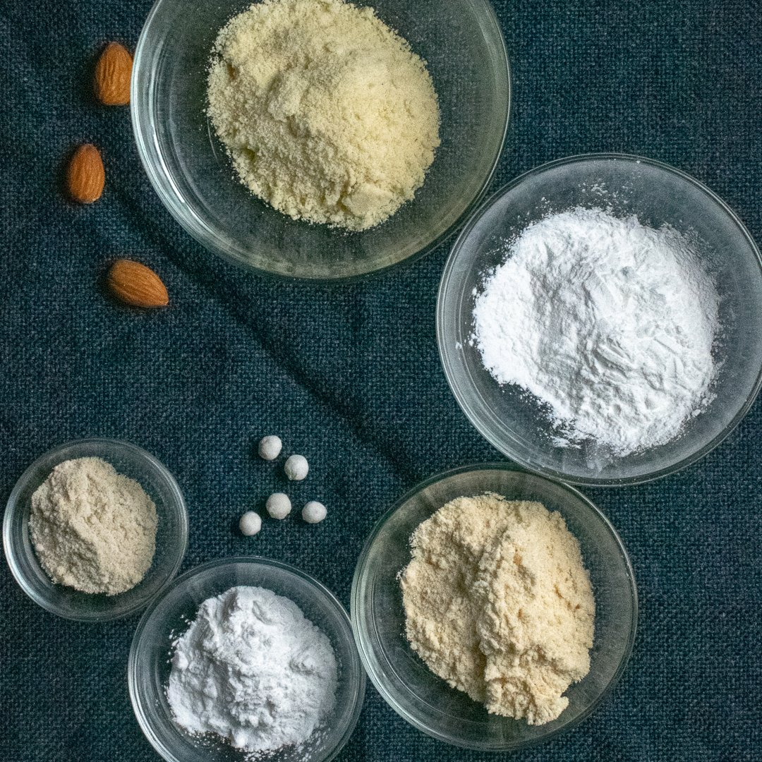 Five gluten-free flours in glass bowls on blue cloth