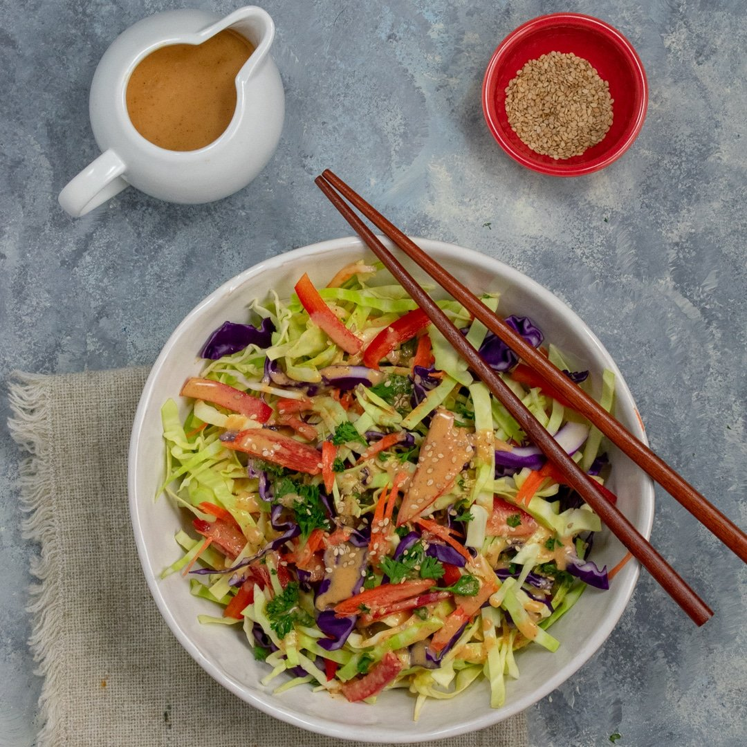 Tangy Ginger-Almond Asian Slaw in white bowl with red bowl of sesame seeds and dressing