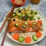 baked miso salmon fillet on white rice with salad on white plate
