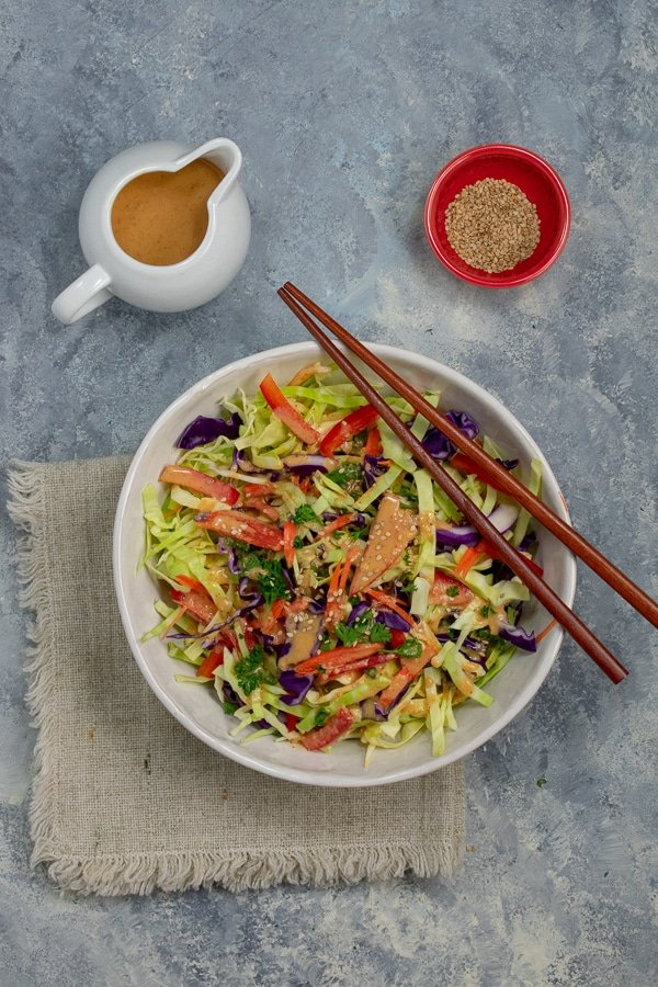 tangy ginger-almond Asian slaw in white bowl from overhead