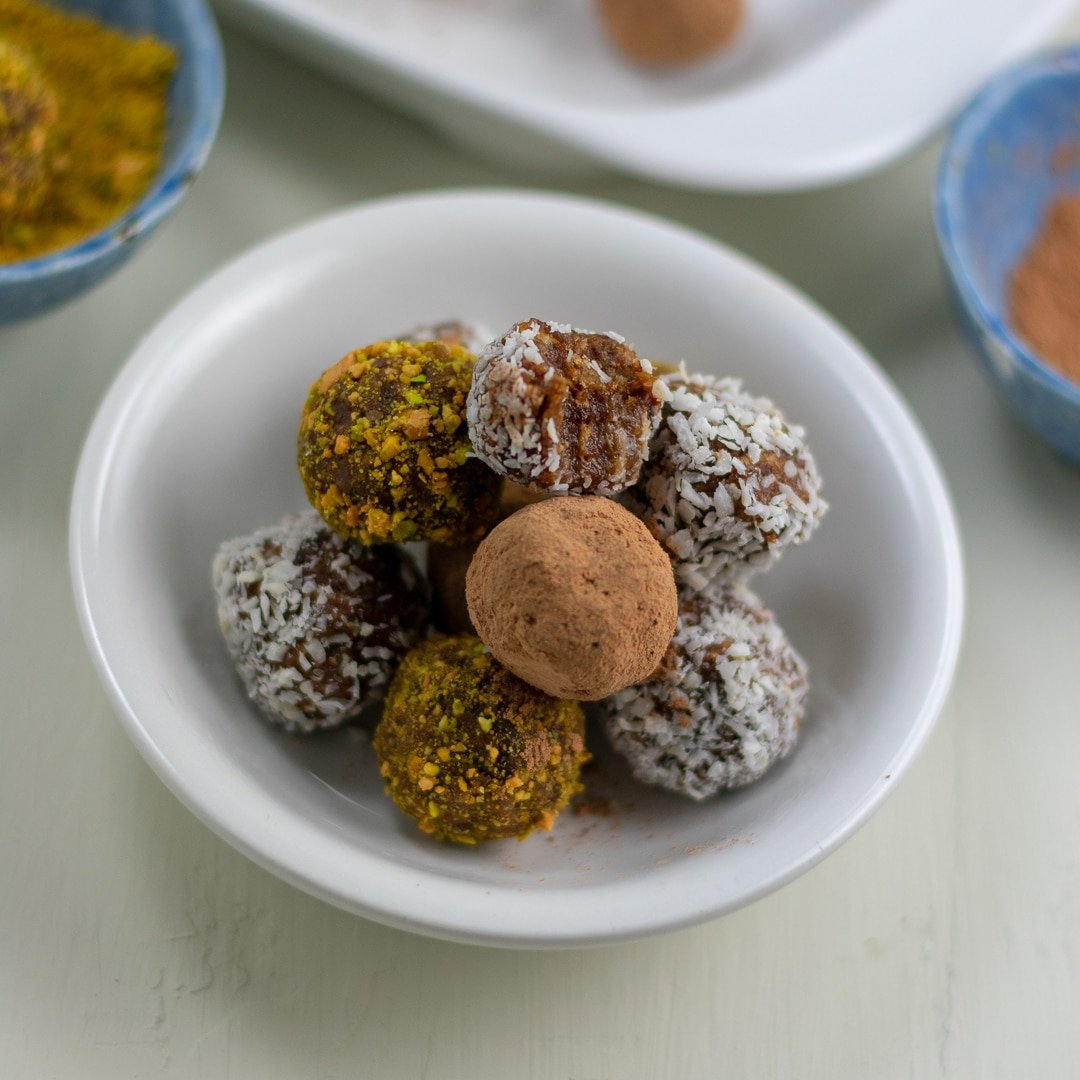 raw date-apricot almond butter bites in white dish