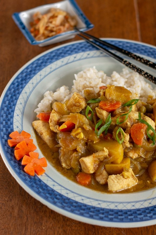 Japanese Chicken curry on rice on a blue plate with chopsticks