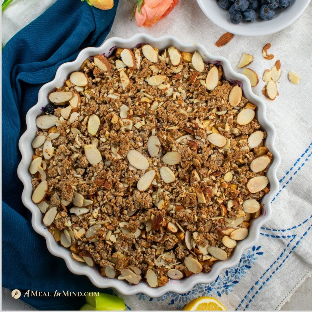 blueberry apple crisp in white tart pan on tablecloth
