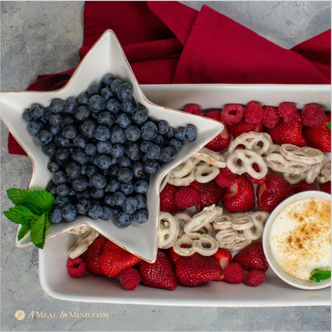 patriotic fruit tray with spiced yogurt dip in white bowl