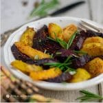 roasted rutabagas and red and gold beets on white dish with gold napkin