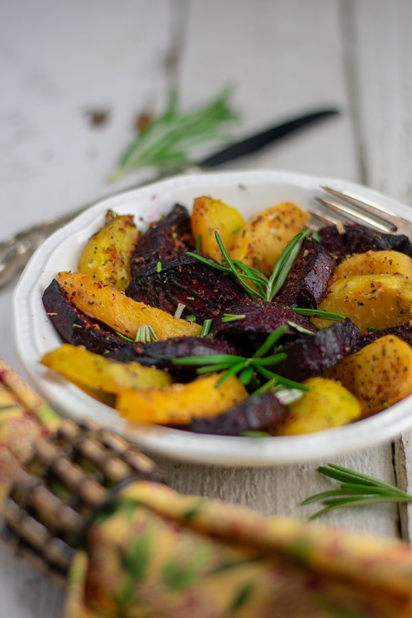 roasted beets and rutabagas on white dish with gold napkin