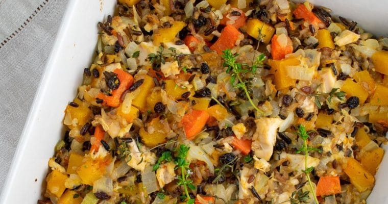 butternut squash chicken rice bake in white baking dish on white napkin