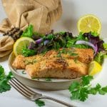easy almond flour crusted salmon on plate with salad greens and lemon