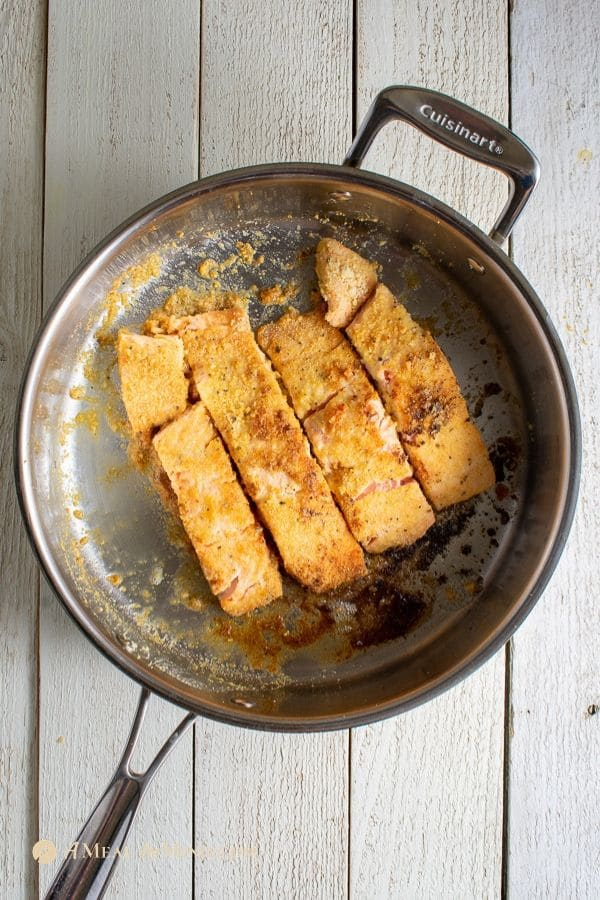seared salmon fillets with almond flour coating in stainless skillet