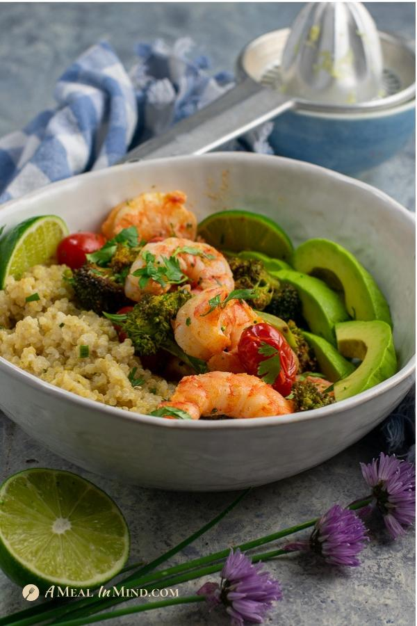 delicious roasted shrimp with broccoli and tomatoes in white bowl with lime