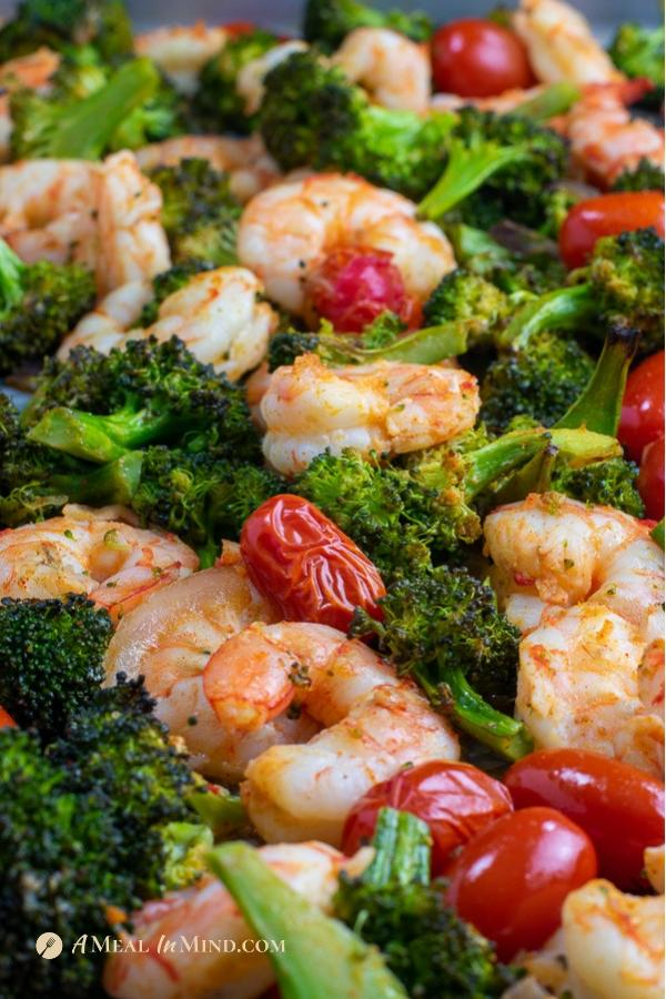 roasted shrimp with broccoli and tomatoes on sheet pan side view