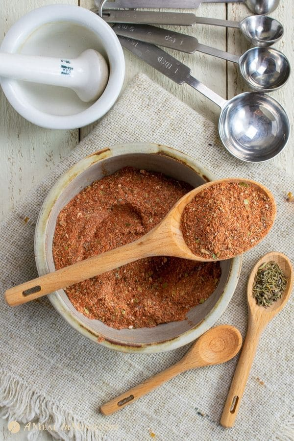 mixed cajun seasoning in clay bowl with wooden spoons