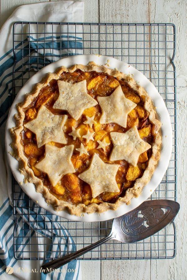 delicious easy colorado peach pie in white ceramic pie plate on wire rack
