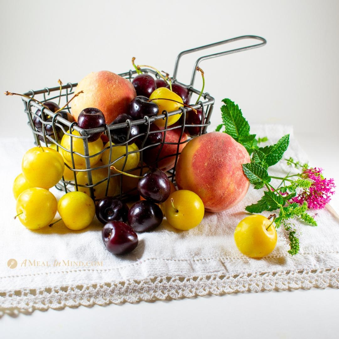 gorgeous organic peaches, plums and cherries in wire basket