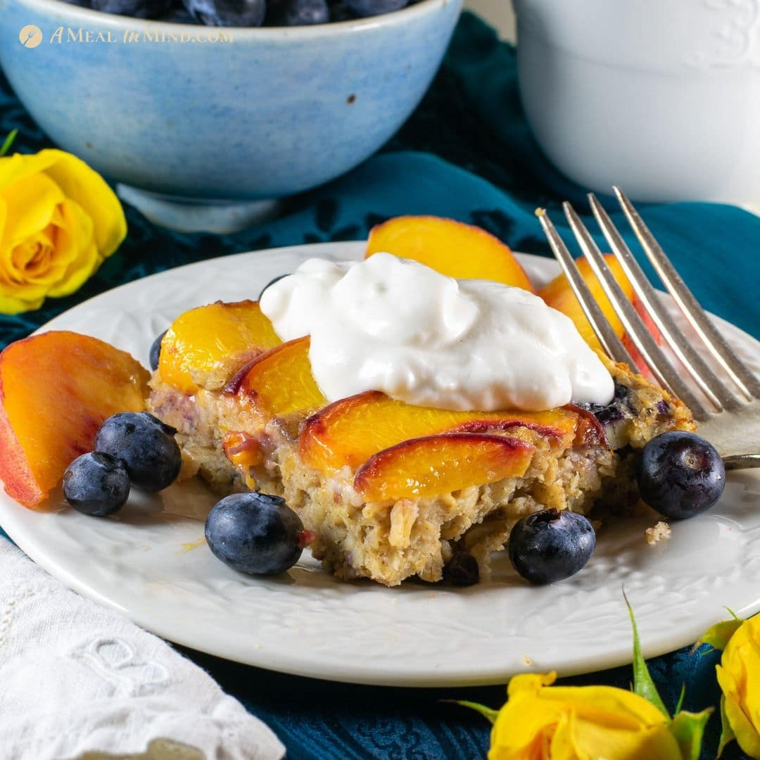 serving of peach oatmeal breakfast clafoutis with almond yogurt on white plate
