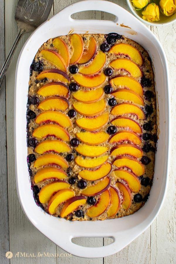 delicious peach oatmeal breakfast clafoutis in white baking pan