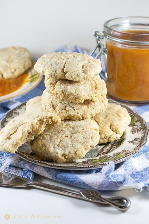 savory almond flour biscuits 5 ingredient in a stack on patterned plate with peach butter