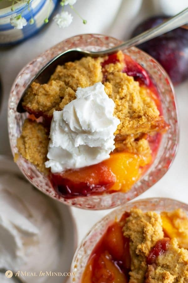easy mouthwatering peach-plum cobbler in glass dish vertical image