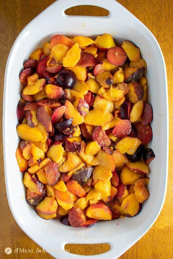cut fruit for mouthwatering peach-plum cobbler in white ceramic baking pan