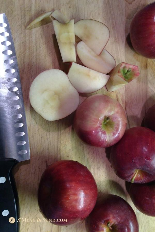 chopping apples for apple butter on a wood board