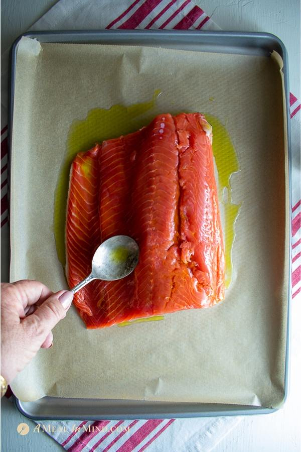 garlic herb salmon baked in parchment side spreading olive oil on fillet in pan