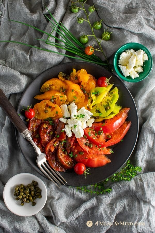 delicious heirloom tomato salad with capers and feta on black plate