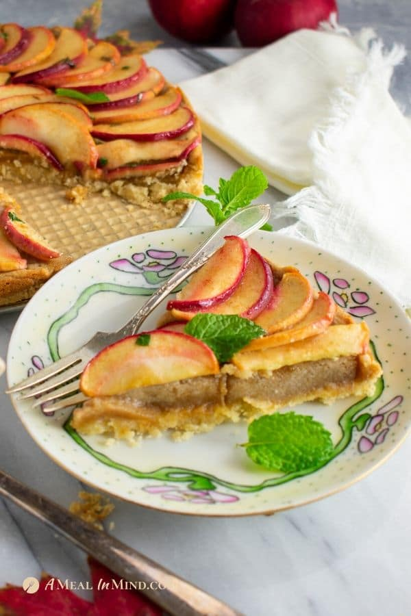 apple marzipan tart with almond crust on flowered plate