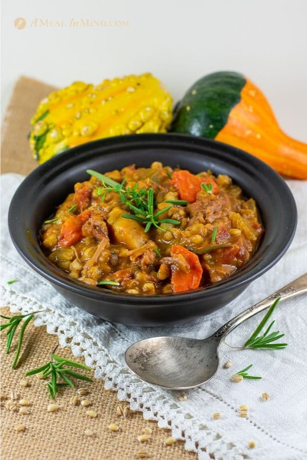 easy beef barley pumpkin stew in black bowl on white cloth