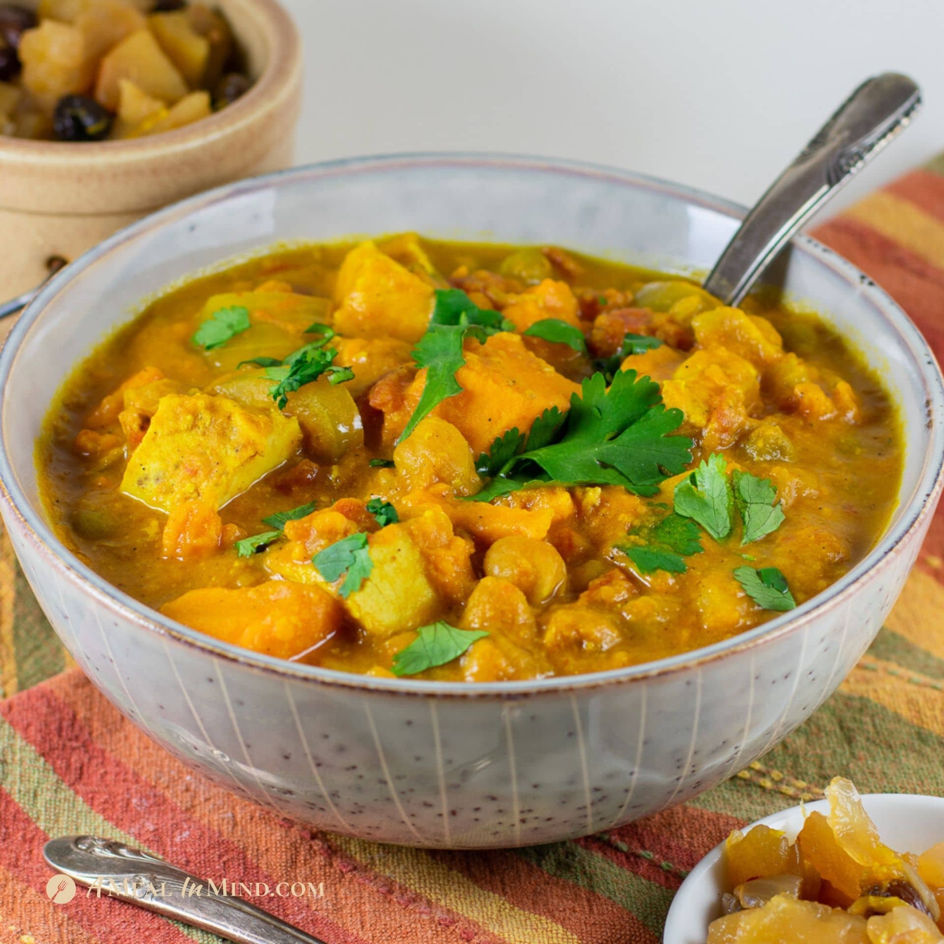 slow cooker sweet potato chicken curry in gray bowl with chutney