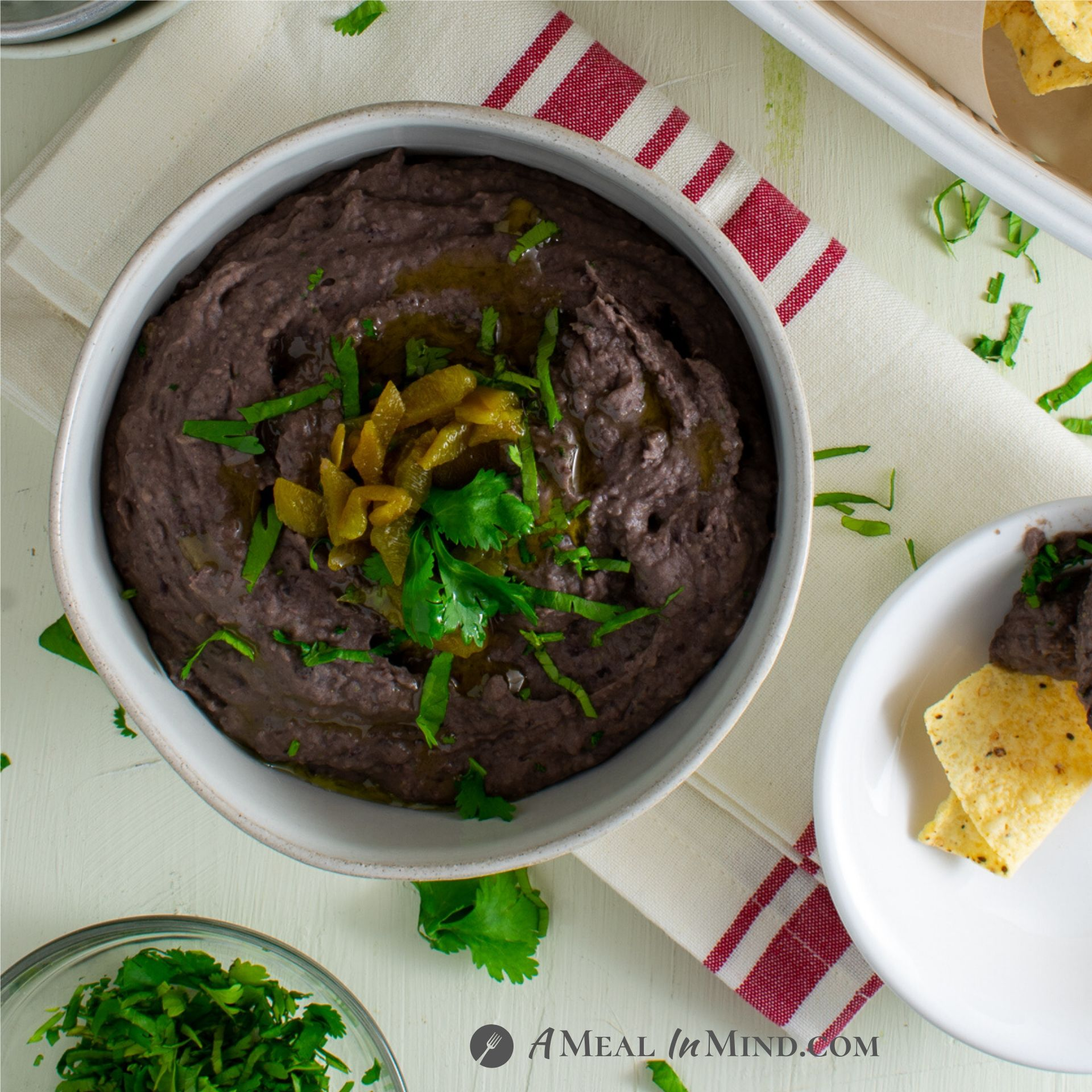 cheese green chile black bean dip in white bowl