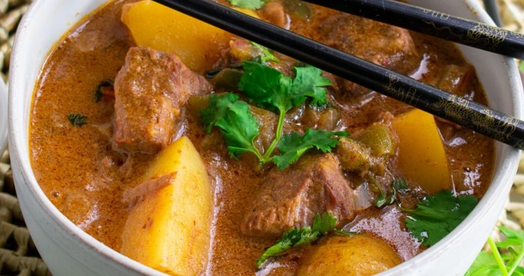 thai massaman beef curry with potatoes in white bowl