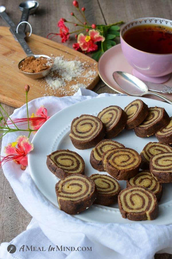 Almond Flour Carob Pinwheel Cookies with a cup of tea and flowers