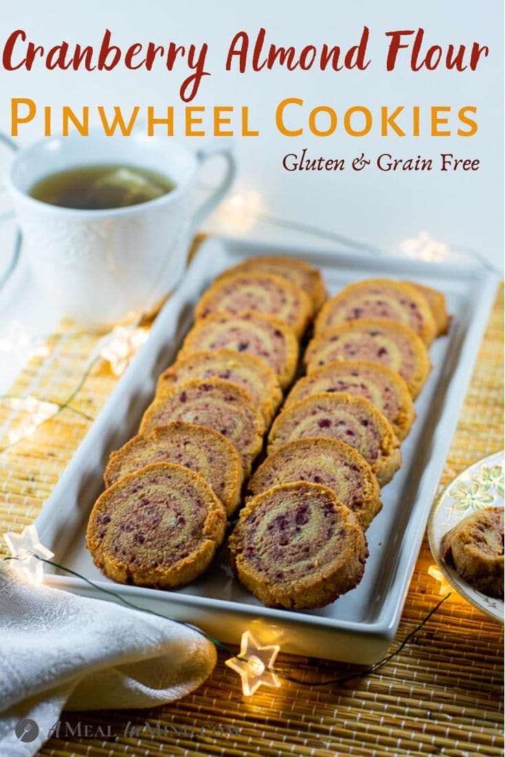 pinterest image of cranberry almond-flour pinwheel cookies on a white platter with a cup of tea