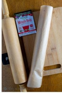 Roll of dough in parchment for cranberry almond-flour pinwheel cookies and MacroLife powder