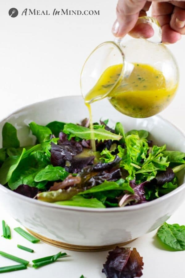 lemony garlic herb dressing being poured from glass server onto salad greens