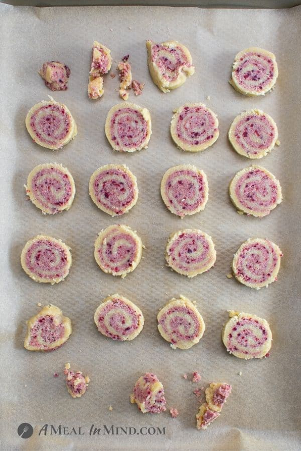 cranberry almond-flour pinwheel cookies sliced and placed on baking sheet