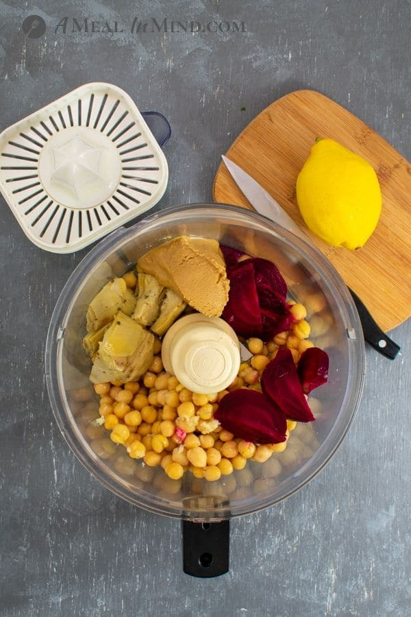 ingredients for Beet Artichoke Hummus in food processor on gray background