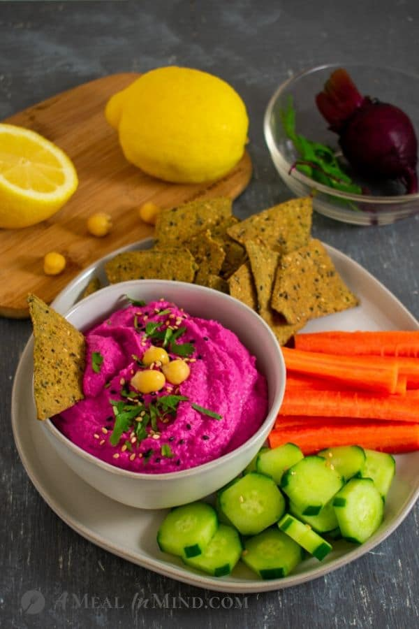 Beet-Artichoke Hummus in small bowl with vegetables and chips