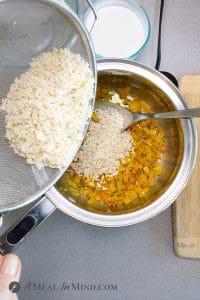 Coconut Turmeric Rice stirring rice into onion mixture