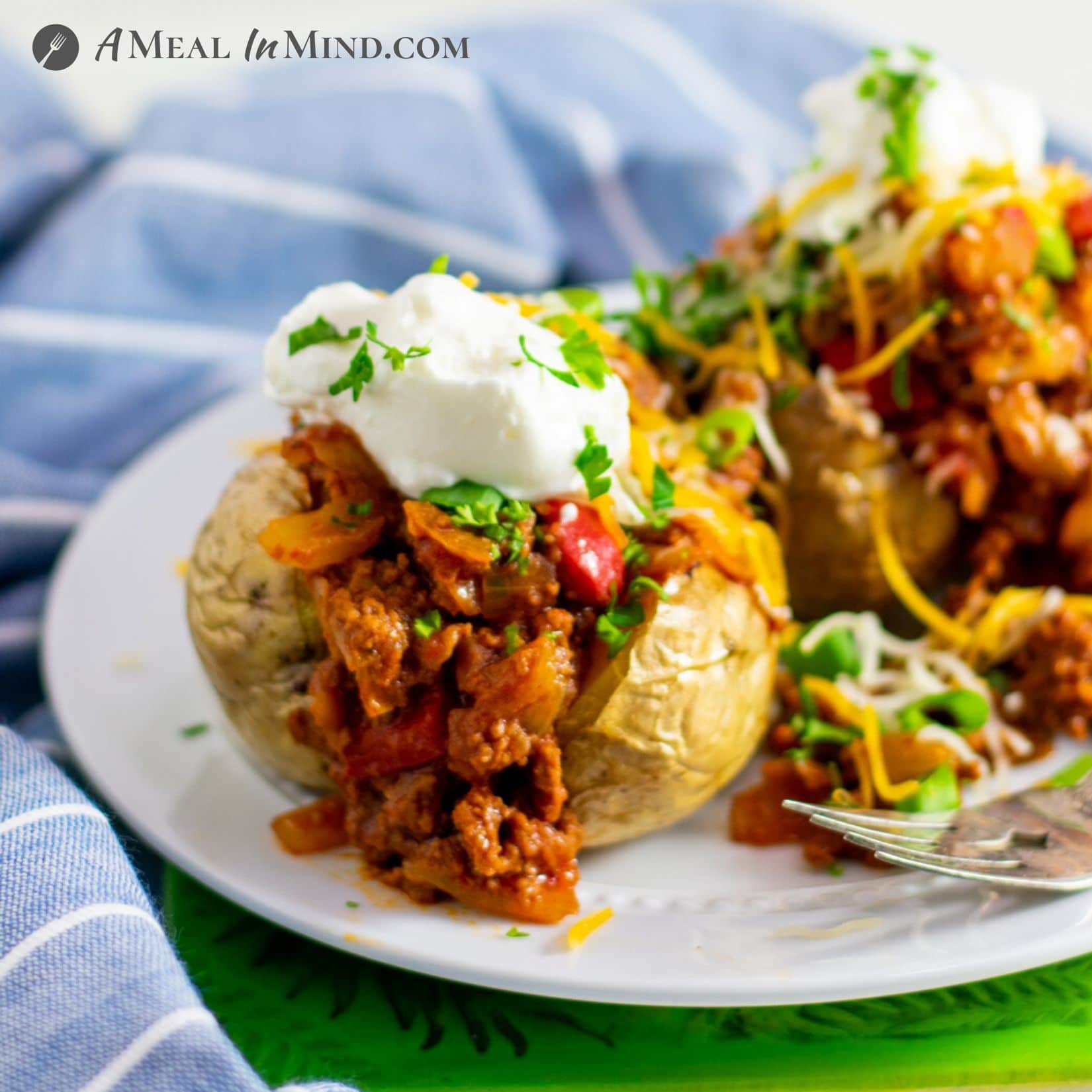 Sloppy Joe Stuffed Potatoes side view on white plate with garnishes